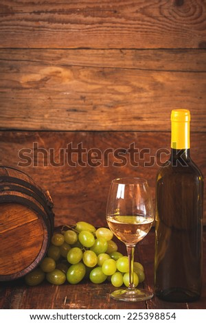 Glass of white wine with bottle and barrel on a rustic wooden table - stock photo