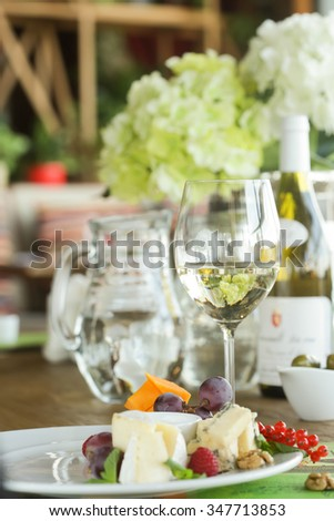 glass of white wine with cheese plate