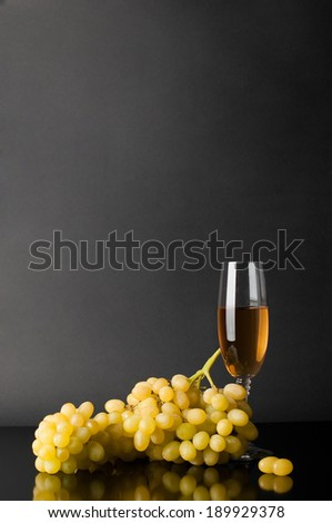 glass of white wine with grapes against dark background