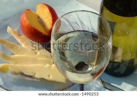 Glass of white wine with green bottle, sliced cheese and fruit on a back - stock photo