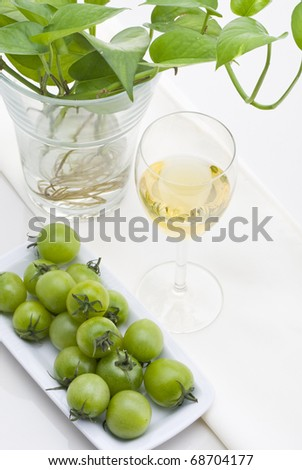 glass of white wine with green plants and small green tomato on white background.