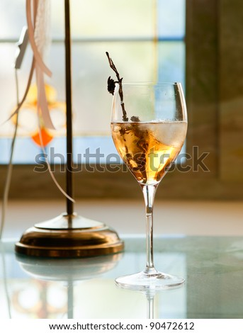 Glass of white wine with ice on the stained glass background - stock photo
