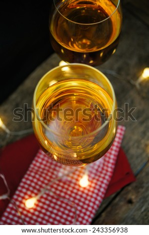 Glass of white wine with lights on old wooden table