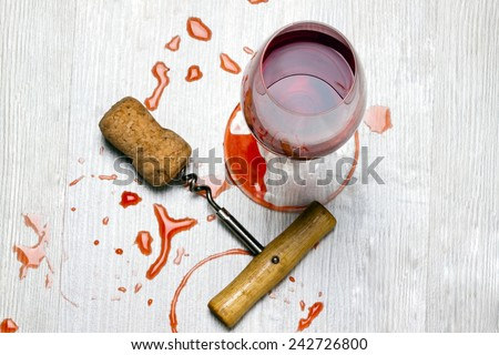 glass of wine and a corkscrew with cork wood surface with stains from wine - stock photo