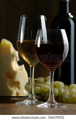 Glass of wine and cheese on a dark background - stock photo