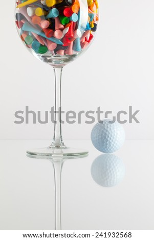 Glass of wine and golf equipments on the glass desk - stock photo