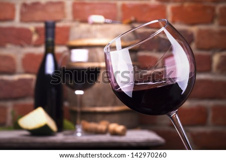 Glass of wine and some fruits, bottle of wine, cheese against a brick wall.
