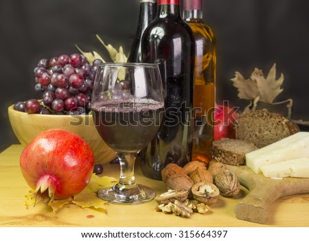 glass of wine, grapes, bottles, walnuts ,leaf, pomegranate