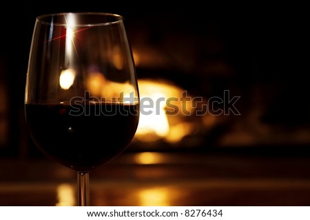 Glass of wine in front of the fireplace - horizontal.  Selective focus, golden glow from the fire.