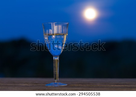 Glass of wine in the moonlight on wooden table outdoor romantic blue sky - stock photo