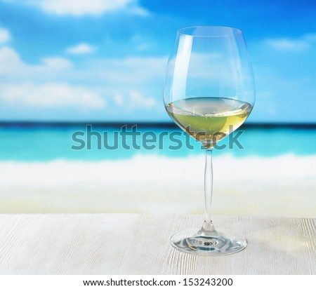 Glass of wine on beach background.