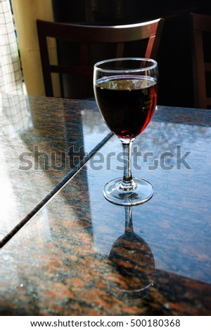 Glass of wine on marble table in Parisian cafe. Selective focus on the reflection.