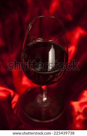 Glass of wine on red silk - stock photo