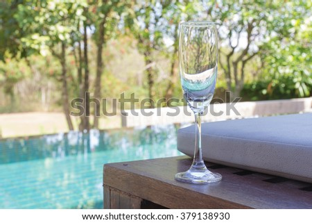 Glass of wine on the bed beside the pool - stock photo