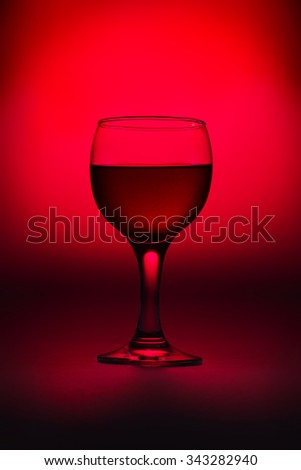 Glass of wine on the red background - stock photo
