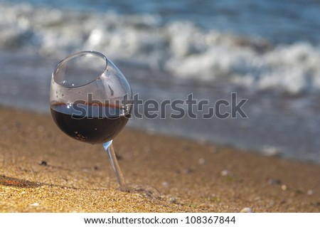 Glass of wine on the see shore in a lovely evening - stock photo