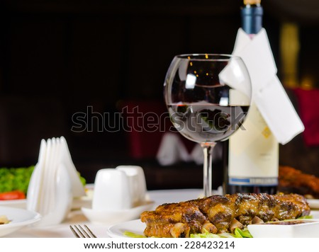 Glass of Wine Served with Grilled Pork Ribs in Restaurant
