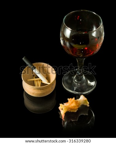 glass of wine, stub and cigarettes on a black background closeup - stock photo