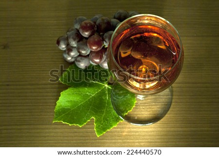 glass of wine with a cluster of red grapes on wooden table background, top view - stock photo