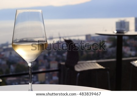glass of wine with city panorama blurred as a background