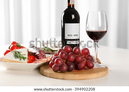 Glass of wine with food on table indoors - stock photo
