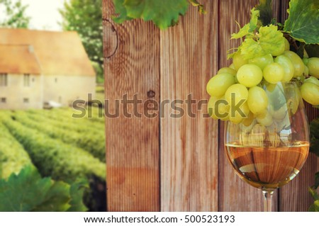 Glass of wine with grape on wooden background