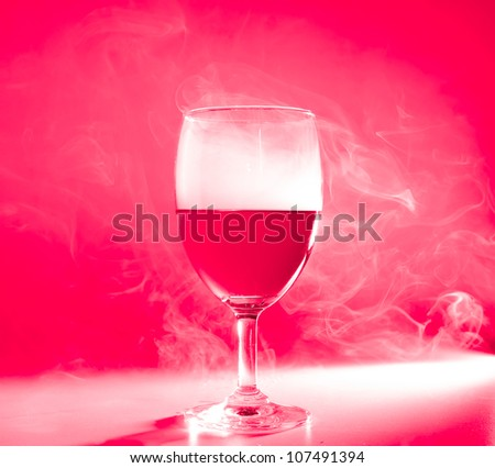 Glass of wine with smoke on red back ground and back light - stock photo