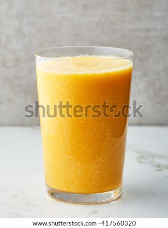 glass of yellow smoothie on gray kitchen table