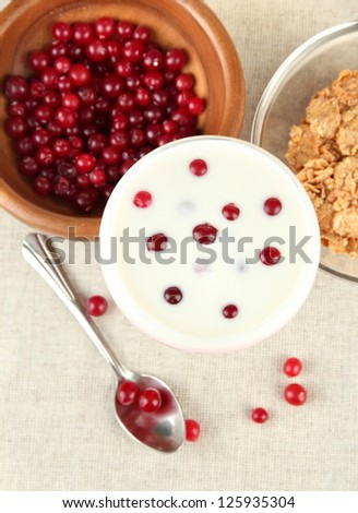 Glass of yoghurt dessert with berries, on tablecloth background