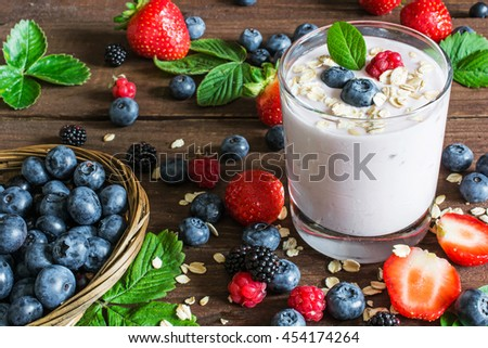 glass of yogurt with whole fresh blueberries, blackberries, raspberries and oatmeal on old rustic wooden table with wicker bowl and many ripe berries. Closeup Detail. - stock photo