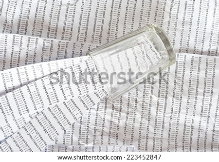 Glass on a background of crumpled DNA sequence with stripes of DNA sequences in it
