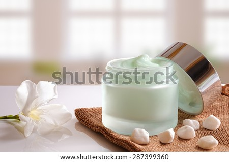Glass open jar with facial or body cream on burlap. with lid, stones and flower. Background windows. Front view. - stock photo