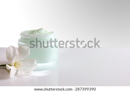 Glass open jar with facial or body cream on white table. with flower and white isolated background. Front view. - stock photo
