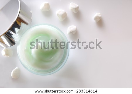 Glass open jar with facial or body cream on white table with small white stones. Top view. White isolated. - stock photo