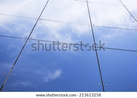 glass panes on facade of trade building reflecting blue sky and clouds - stock photo