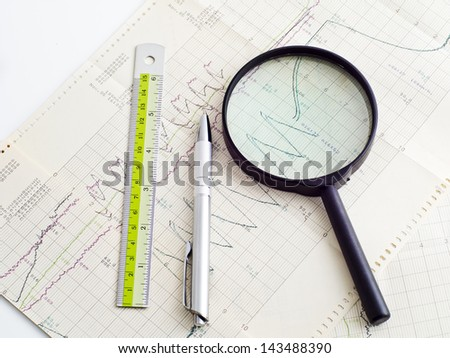 glass pen and ruler on scientific graph to analysis the results