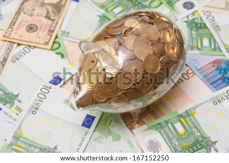 Glass piggy bank full of golden coins over a background made of Euro and Dollar bank notes bills. - stock photo