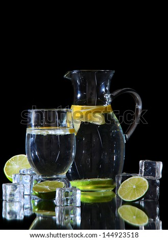 Glass pitcher of water and glass isolated on black - stock photo