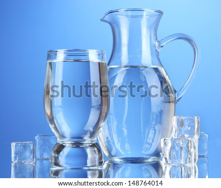 Glass pitcher of water and glass on blue background - stock photo