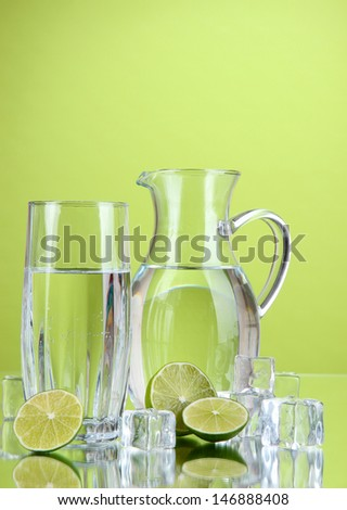 Glass pitcher of water and glass on green background - stock photo