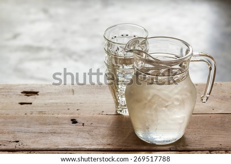 Glass pitcher of water and glass on wooden table background. - stock photo