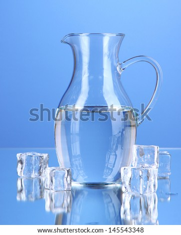 Glass pitcher of water on blue background