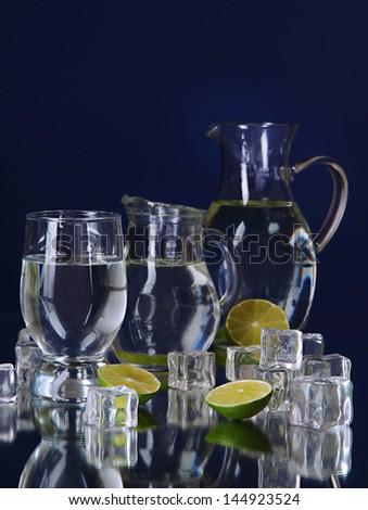 Glass pitchers of water and glass on blue background - stock photo