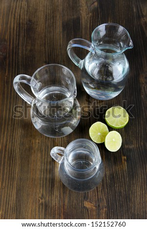 Glass pitchers of water on wooden table close-up - stock photo