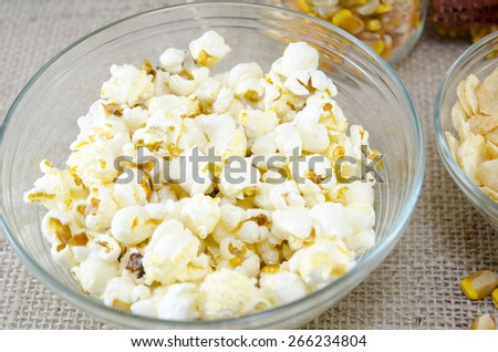 Glass plate full with popcorns with cornflakes and corn in the background - stock photo
