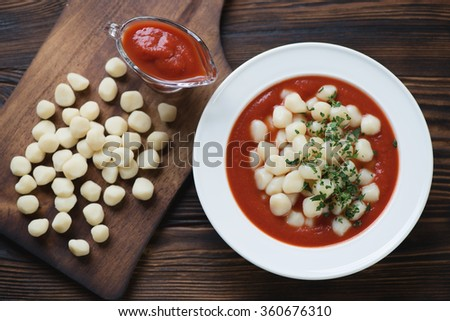 Glass plate of italian gnocchi with tomato sauce, above view - stock photo