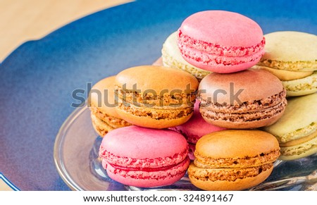 Glass plate with colorful raspberry, chocolate, pistachio and coffee macarons.