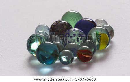 Glass playing marbles different colors,shadows, light against the window. - stock photo