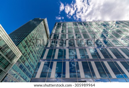 Glass reflective office buildings against blue sky with clouds and sun light - stock photo