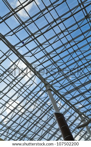 glass roof of a modern building and blue sky - stock photo